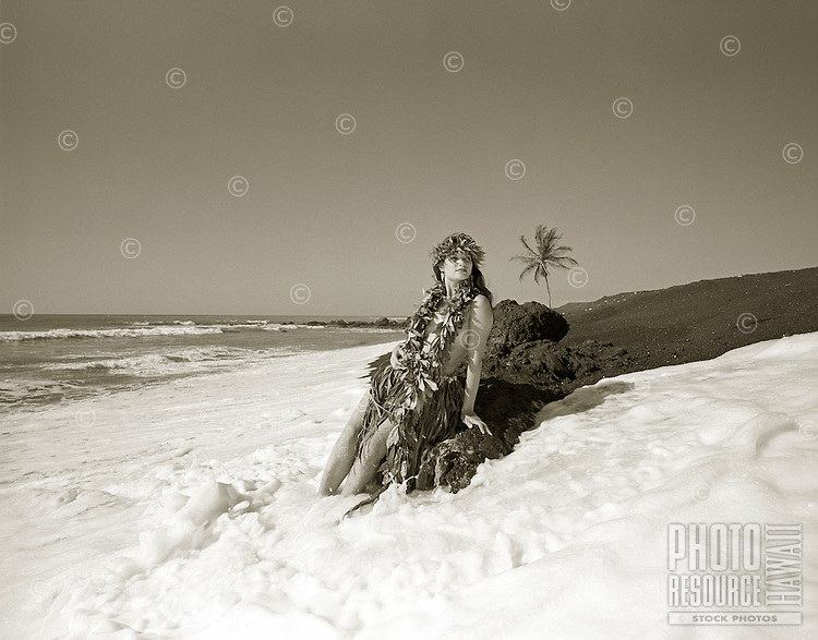 Young Hawaiian girl on a black sand beach with the foaming water at her feet.