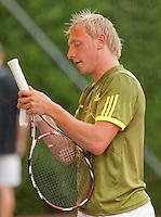 12-8-09, Den Bosch,Nationale Tennis Kampioenschappen, 1e ronde,  Arko Zoutendijk  rolt een nieuw teepje om het handvat van zijn drijfnatte racket in de stromende regen