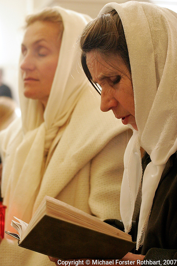 Two women pray and read from the Bible as Ukrainians crowd into the Church of the Assumption (Uspensky Cathedral) in the Pechersk Lavra monastery in Kyiv, Ukraine for an all-night Eastern Orthodox Easter service, on April 8, 2007.<br /> <br /> &copy; Michael Forster Rothbart<br /> www.mfrphoto.com <br /> 607-267-4893 o 607-432-5984<br /> 5 Draper St, Oneonta, NY 13820<br /> 86 Three Mile Pond Rd, Vassalboro, ME 04989<br /> info@mfrphoto.com<br /> Photo by: Michael Forster Rothbart<br /> Date: 4/2007    File#:  Canon 20D digital camera frame 2220