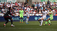 Sergio Aguero of Manchester City (R) is held back by Jordi Amat of Swansea City while Kristoffer Nordfeldt (L) looks on during the Swansea City FC v Manchester City Premier League game at the Liberty Stadium, Swansea, Wales, UK, Sunday 15 May 2016