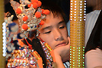 Donggang, Taiwan -- Bored worshiper trying to keep his eyes open in the early morning hours.