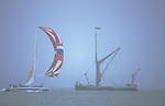 Cowes Regatta, Isle of Wight. An old Thames barge meets a Maxi racing yacht.  The English Season published by Pavilon Books