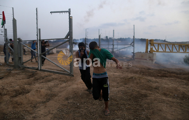 "Palestinian protestors gather after tearing down a section of a border fence between Israel and the Gaza Strip during clashes with Israeli security forces on October 12, 2015, east of Bureij in central Gaza. Palestinian foreign minister Riad al-Malki accused Israel of seeking to spark ""a third intifada"", as violence again flared in Jerusalem, the West Bank and the Gaza Strip. Photo by Yasser Qudih"