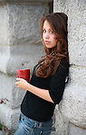 pretty young woman with long brown hair holds a coffee cup outdoors in morning shade
