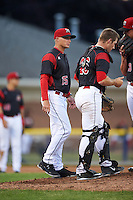 Batavia Muckdogs pitching coach Chad Rhoades (15) walks out to the mound to talk with pitcher Trenton Hill (39) and catcher David Gauntt (46) during a game against the West Virginia Black Bears on June 28, 2016 at Dwyer Stadium in Batavia, New York.  Batavia defeated West Virginia 3-1.  (Mike Janes/Four Seam Images)