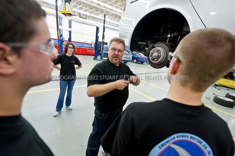 11/4/2010--Shoreline, WA, USA..Bob Biesiedzinski, a teacher (center), works with students Gabriel Rios, 18 (left, foregournd) ,  Mark Jensen, 19 (right, foreground) and Christine Neuner, 20 (bbackground) on a Honda Acura's brake system at the Shoreline Community College just north of Seattle, WASH...The students are enrolled on a Skills for America jobs training program at the Shoreline Community College  that trains and places students for automotive technician jobs at car dealerships, working with local Honda and Toyota dealerships among others...©2010 Stuart Isett. All rights reserved