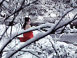 Beautiful woman in red kimono with bare shoulders sitting on snow in a beautiful snowy winter nature scenery by a river