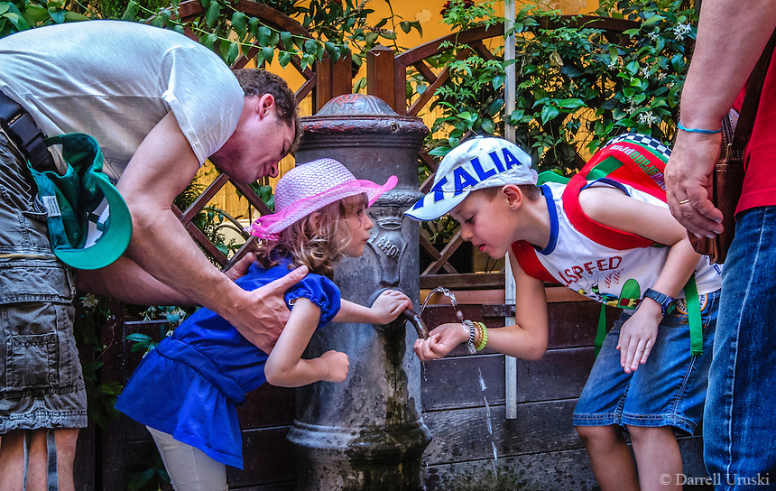 Urban Street Photography of two children capturing a drink from one of the many water fountains in Rome. The Nasoni, water fountain which translates as &ldquo;big noses,&rdquo; are spread all over the city of Rome. <br />