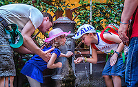 Urban Street Photography of two children capturing a drink from one of the many water fountains in Rome. The Nasoni, water fountain which translates as &ldquo;big noses,&rdquo; are spread all over the city of Rome. <br /> The ITALIA, cap, and colours on his backpack really add character to this traditional Italian scene.