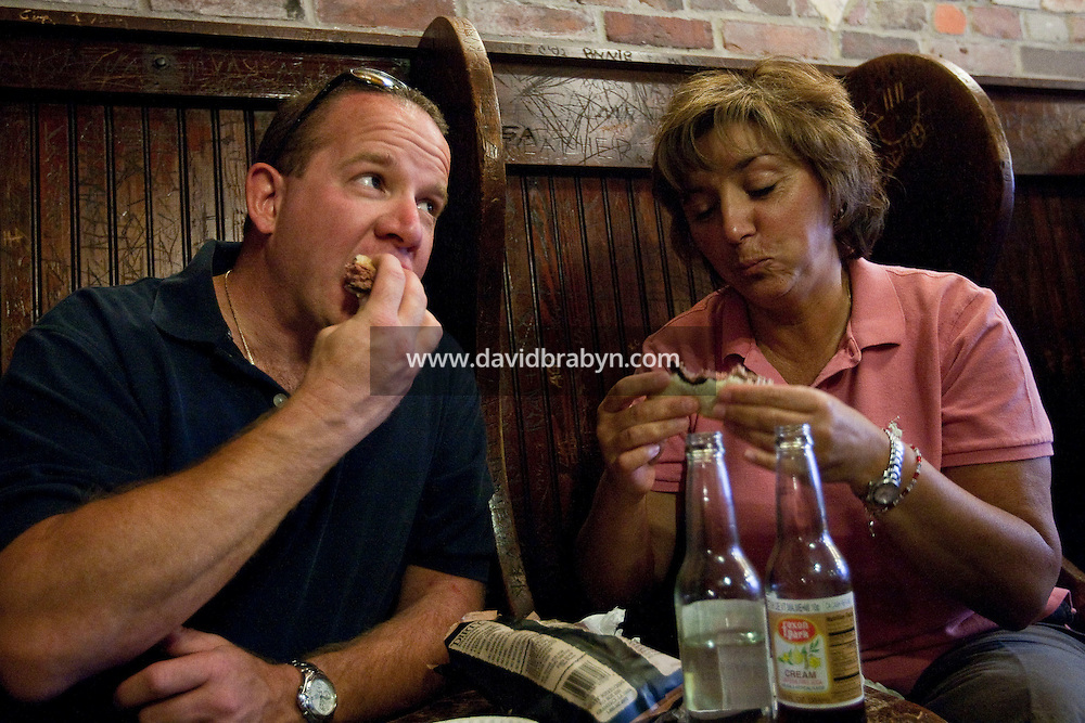 Clients eat hamburgers at Louis' Lunch  hamburgers joint in New Haven, CT, USA, 26 May 2009.