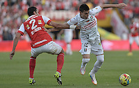 BOGOTÁ -COLOMBIA, 04-05-2014. Jose J de la Cuesta (Izq) de Independiente Santa Fe disputa el balón con Daniel Hernandez (Der) del Once Caldas durante partido de vuelta por los cuartos de final de la Liga Postobón  I 2014 jugado en el estadio Nemesio Camacho el Campín de la ciudad de Bogotá./ Independiente Santa Fe player Jose J de la Cuesta (L) fights for the ball with Once Caldas player Daniel Hernandez (R) during second leg match for the quarterfinals of the Postobon League I 2014 played at Nemesio Camacho El Campin stadium in Bogotá city. Photo: VizzorImage/ Gabriel Aponte / Staff