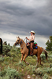 USA, Wyoming, Encampment, a cowgirl rides a horse through the sage brush, Abara Ranch