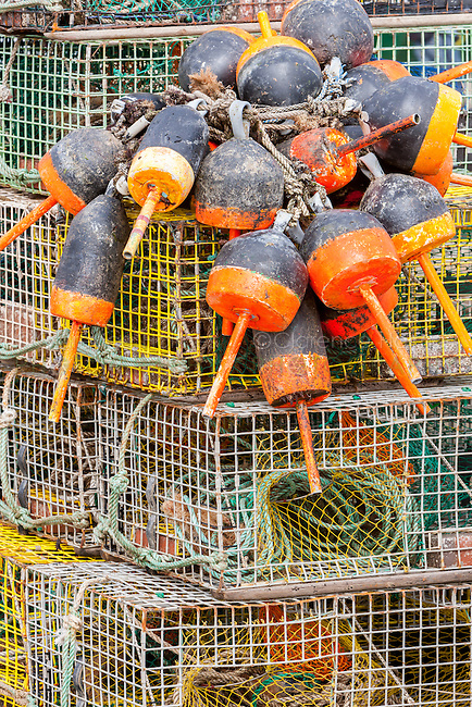 Stacked lobster traps and buoys on a pier in Maine.