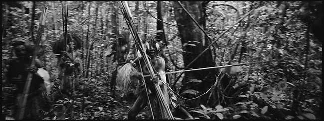 """A group of native tribesmen surrond the """"First Contact"""" group, West Papua, Indonesia, September 2004."""