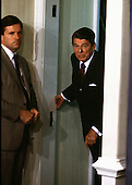 U.S. President Ronald Reagan peeks from the door of the White House Briefing Room during a press briefing by U.S. Secretary of State George Shultz on 5 August, 1987..Credit: Arnie Sachs / CNP
