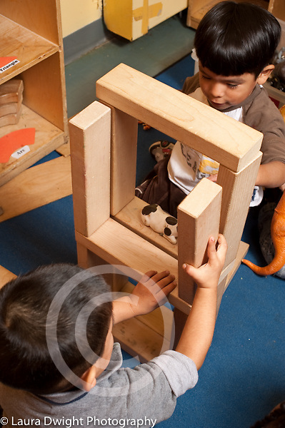Education prechool 3-4 year olds two boys building with wooden blocks working together vertical