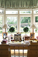 A sunny bay window with a vintage desk and bamboo chair overlooks the garden