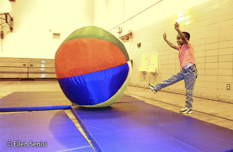 MR / Schenectady, NY                                  .Yates Arts-in-Education Magnet School (urban school).Pre-Kindergarten class; NYS Universal Pre-K Program.Girl (5, African-American) kicks big ball in gym class..Smi14.Color and light manipulated  digitally..©Ellen B. Senisi