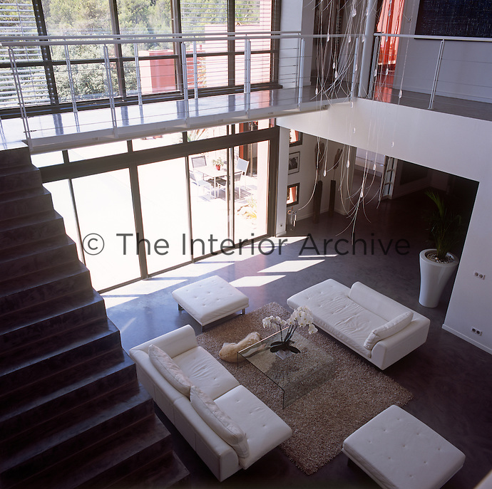 An elevated view of a modern open plan living room with a staircase to one side that leads up to a gallery walkway around the upper floor. Full height windows allow plenty of light into the room. The room is simply furnished with white upholstered seating.