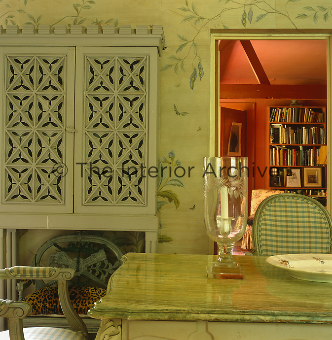 The elegant dining room with its hand-painted wallpaper opens onto the warm terracotta of the adjoining library