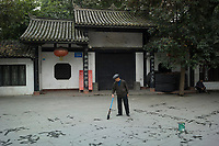 "Meishan, Sichuan province, China, October 2014 - An elderly man practices calligraphy in front of the Three Su Temple which was built to commemorate famous Song dynasty poet and politician Su Dongpo and his father and brother who were also notable writers (the ""three Su""). Su Dongpo was native of Meishan."