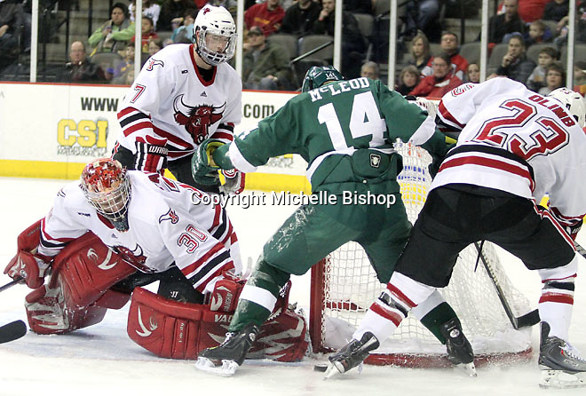 UNO goalie John Faulkner eyes a loose puck as Bemidji State's Aaron McLeod and UNO's Eric Olimb battle at the side of the net. UNO and Bemidji State skated to a 2-2 tie Friday night at Qwest Center Omaha. (Photo by Michelle Bishop)
