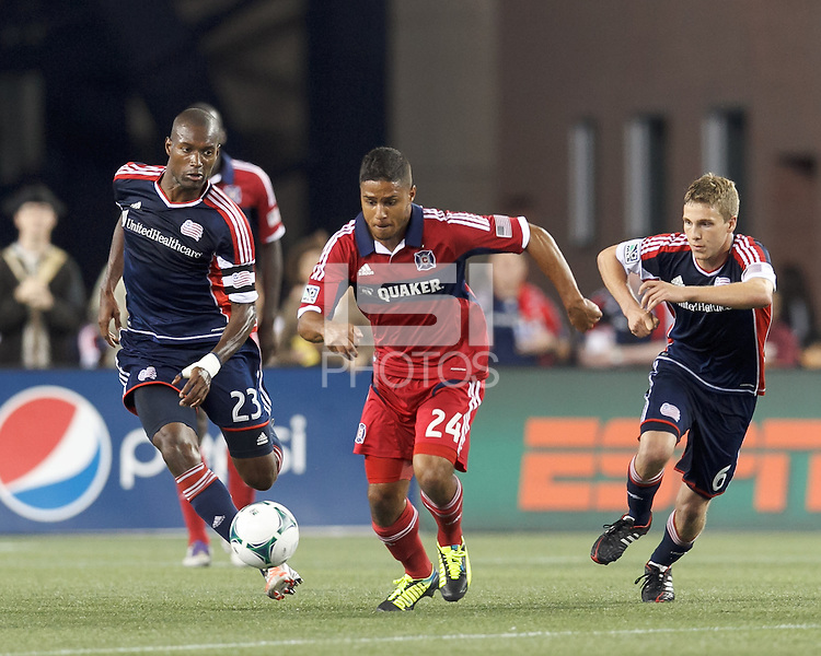Chicago Fire substitute forward Quincy Amarikwa (24) works to clear ball as New England Revolution defender Jose Goncalves (23) and New England Revolution midfielder Scott Caldwell (6) close. In a Major League Soccer (MLS) match, the New England Revolution (blue) defeated Chicago Fire (red), 2-0, at Gillette Stadium on August 17, 2013.