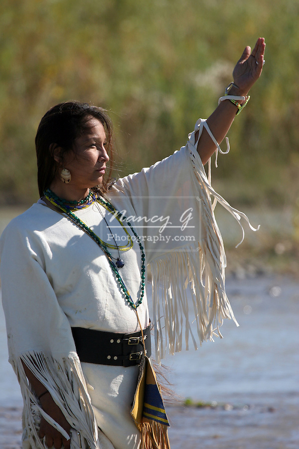 A Native American Indian women worshiping the sun while standing in the river in South Dakota