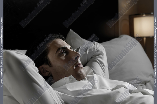 Young man lying alone in bed with thoughtful expression