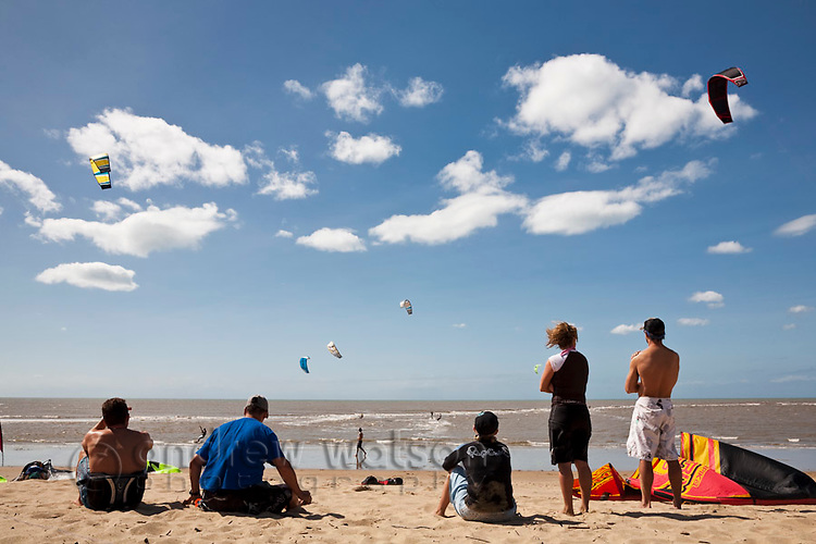 Group watching kite-surfers at Yorkeys Knob beach.  Cairns, Queensland, Australia