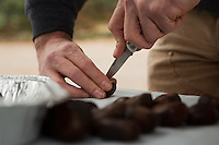Friends of the Wissahickon Volunteer Coordinator Dan Mercer score chestnuts that are about to be roasted on an open fire at the Winter in the Wissahickon event hosted by Friends of the Wissahickon. (Dave Tavani/for NewsWorks)