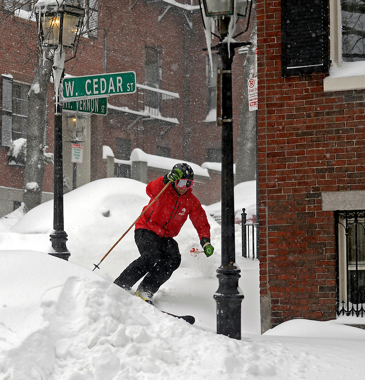 Boston resident Mark Wallace makes a turn while skiing in Boston's Beacon Hill neighborhood after a blizzard dumped over two feet of snow in the city on Tuesday, January 27, 2015. Photo by Christopher Evans