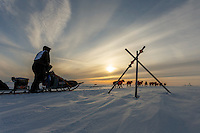 Ken Anderson runs past a tripod trail marker on the trail several miles from the Nome finish line near sunset on Wednesday March 17, 2015 during Iditarod 2015.  <br /> <br /> (C) Jeff Schultz/SchultzPhoto.com - ALL RIGHTS RESERVED<br />  DUPLICATION  PROHIBITED  WITHOUT  PERMISSION