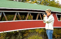 Tourist taking pictures at small curved covered bridge in Jackson, New Hampshire