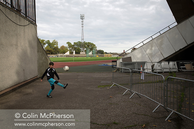 A young boy kicking football outside the grandstand at Meadowbank Stadium in Edinburgh, before Edinburgh City played host to Spartans in a Lowland League fixture. The host won the match 1-0 with a late goal by Ousman See, despite playing for the last 30 minutes with 10 men after Ross Allum was sent off. The wind kept the reigning champions side clear at the top of the league.