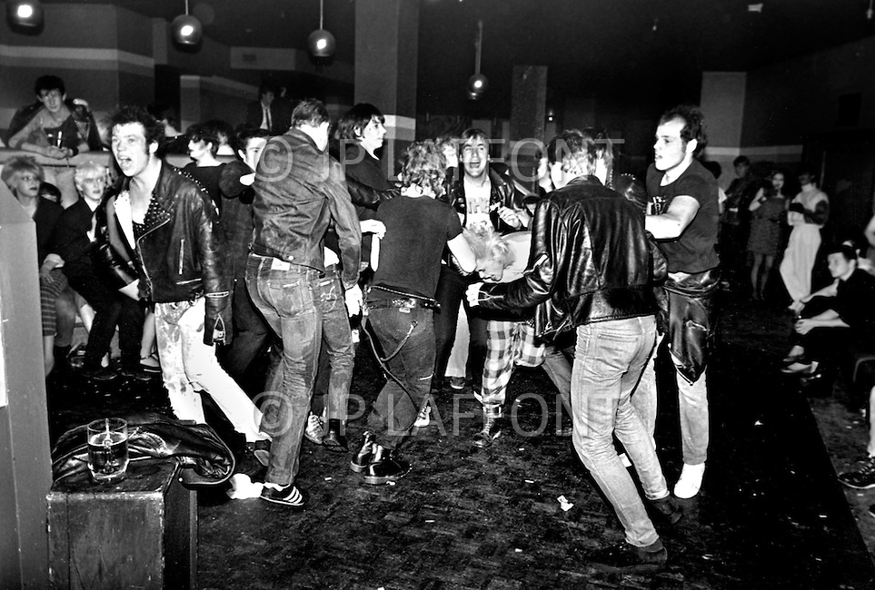 """England. August, 1981. Land Without a Hope. The Derby night-club of Newcastle: The famous """"Pogo"""", a violent dance. All steps are allowed, but only male dancers. Here, a group of metal-heads, or black-jackets. A catastrophic economic situation with three million unemployed, probably four million next year, Great Britain is bowed beneath the weight of the crisis. Factories and even whole cities no longer exist on the conomic map. The young poeple, who are the chief victims of this situation, are sinking into a state of despair. Gangs are multiplying, and in the streets, in night-clubs, it is the reign of the brutal metalheads, the provocative punks, the violent skinheads...and the silly sweetness of the """"romantics""""."""