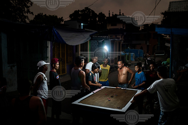 Residents playing a game based on pool using a homemade table at Manila North Cemetery.  Manila North Cemetery is home to thousands of 'informal settlers' who have built shacks using in and around the mausoleums, crypts and tombs. In comparison to the city's dangerous shantytowns the cemetery is relatively quiet and safe. However, water must be collected from a few public wells and the electricity supply is erratic, usually stolen from mains cables. In the summer the sweltering heat drives people to sleep outside often on top of the tombs.<br /> <br /> Some of the residents live in the crypts and mausoleums of wealthy families, who pay them a stipend to clean and watch over them. Others make a living carving headstones or selling candles to visitors and helping out at funerals as the daily life of the cemetery goes on around the people who live there.
