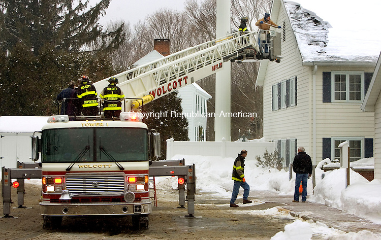 WOLCOTT, CT. 26 January 2011-012611SV01--With the help of firefighters, Joe Golden of the maintenance department clears snow from the roof of the town hall in Wolcott Wednesday. Water from the roof was leaking into the finance department.<br /> Steven Valenti Republican-American