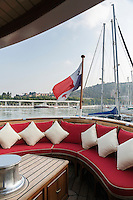 A comfortable banquette furnishes the stern upholstered with cheerful red squab cushions.  La Sultana flies under a Panamian flag