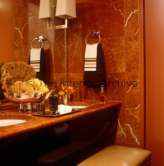 The reddish-brown veined marble walls and surfaces in this bathroom have created a subtly masculine feel