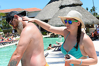 Laura Phelps helps groomsman Danny Arnot with sunscreen after Thursday's run-through. Much sunscreen will be used this week.