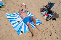 Ian Towle (center, from front) read on the beach near cars at Herring Cove Beach in the Cape Cod National Seashore outside of Provincetown, Mass., USA, on Fri., July 1, 2016. Portions of the parking lot have been closed after land eroded during storms earlier this year. Ian has a piece of eroded asphalt weighing down a corner of his beach blanket.