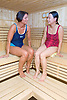 Two women relaxing in the sauna at their sports leisure centre,