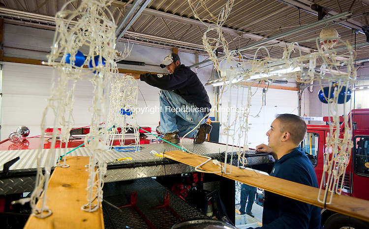 WINSTED, CT--- -121915JS03--Members of Cascade Hose Engine 4 in Winsted, firefighter Michael Cyr, left, and Lt. Jeffrey Liskin, right, get their truck decorated for 11th annual Winsted Fire Department &quot;Gator&quot; Christmas Parade on Saturday. The parade continues to honor the tradition of former firefighter Gaeton &quot;Gator&quot; Gangi who started the parade in 2004 as a community Christmas parade. <br /> Jim Shannon Republican-American