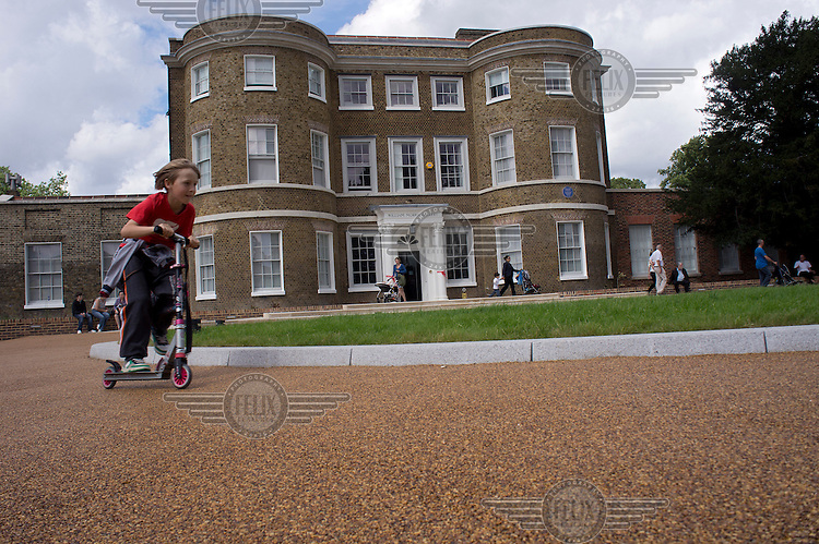 A child rides a scooter in the grounds of the William Morris Gallery in Walthamstow, London.