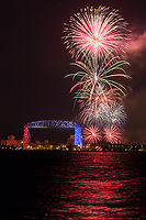 """""""Duluth's Grand Fireworks""""<br /> <br /> Duluth, Minnesota puts on a grand fireworks display over the harbor each Independence Day. The ample Lake Superior shoreline and hillsides give viewers many choices for prime vantage points. To top it off, the Aerial Lift Bridge is specially lit in red, white, and blue just this one night. It is spectacular!"""