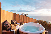 BNPS.co.uk (01202 558833)<br /> Pic: UniqueHomeStays/BNPS<br /> <br /> Pictured: Outside there is a two person hot tub<br /> <br /> A couple who spent £450,000 on turning a 'rotting shed' into an exclusive seaside bolthole hope to recoup their money - by renting it out for £3,150 a week. <br /> <br /> Tracey Gilpin and Peter Burridge went out on a limb when they bought the 60-year-old wooden shack for a whopping £220,000.<br /> <br /> Despite its ramshackle condition, the cabin could command such a hefty asking price as it is located halfway up a cliff with stunning views of Whitsand Bay in Cornwall.<br /> <br /> But in order to make the coastal chalet a viable holiday let the couple had to demolish it and build a new one from scratch.