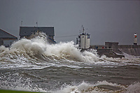 Pictured: Waves crash against the promenade wall by Porthcawl Lighthouse, Wales, UK. Friday 12 October 2018<br /> Re: Strong winds and rain caused by Storm Callum in south Wales, UK.