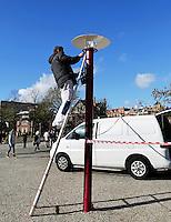 Man schildert de lampen op het Museumplein in Amsterdam