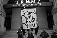A protestor holds up a sign in front of the Trump International Hotel during the Women's March on Washington the dat after Inauguration Day in Washington, DC on Jan. 21, 2017.